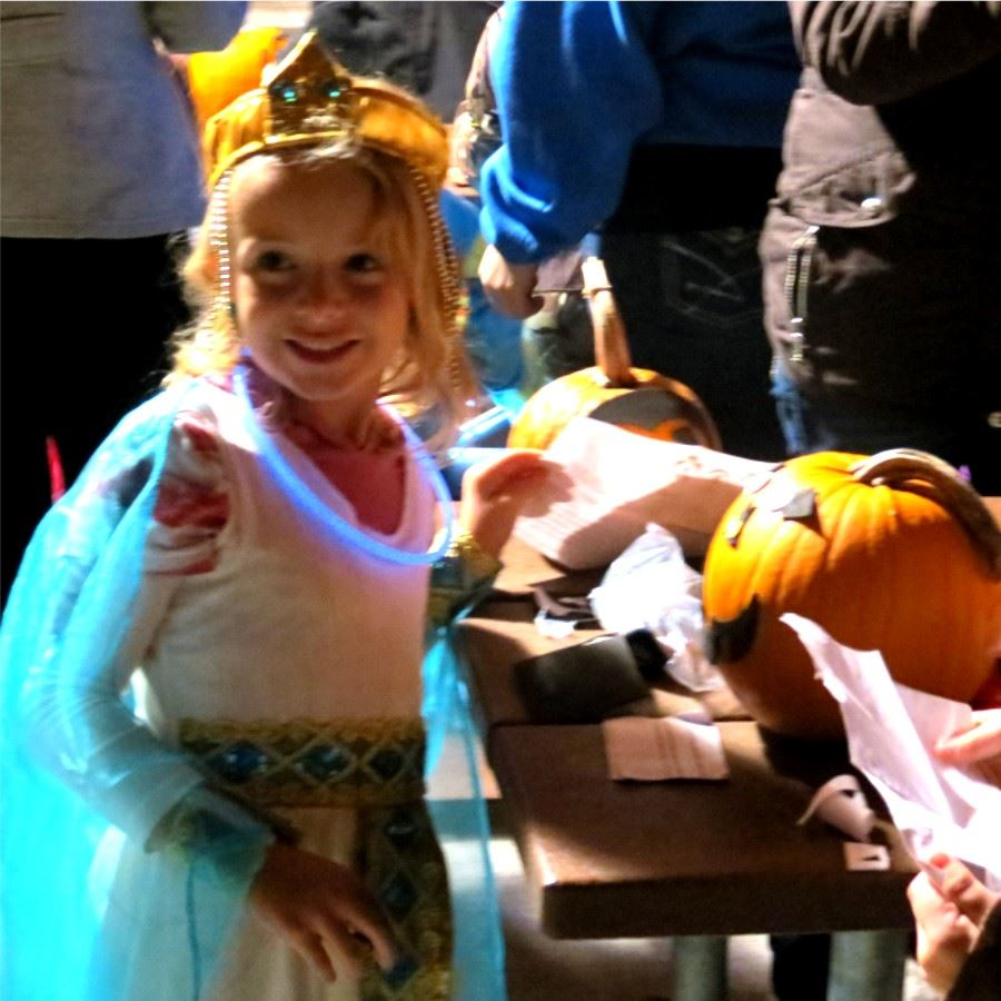Girl carving a pumpkin at Flashlight Pumpkin Hunt