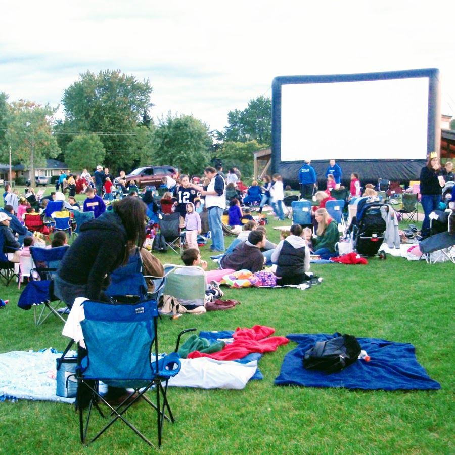 Crowd of people gathering in front of outdoor movie screen