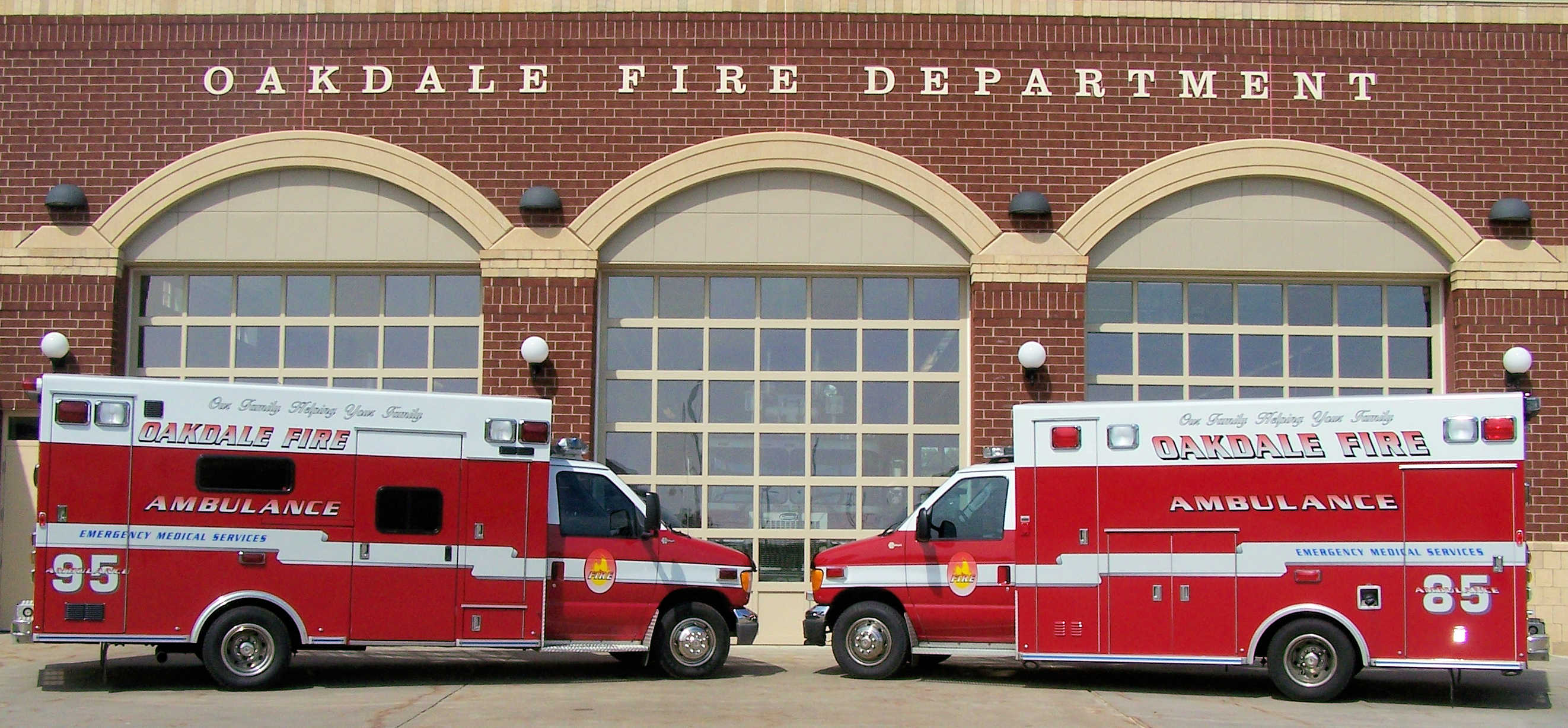 Two Oakdale fire department ambulances parked in front of a fire station