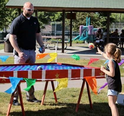 Police Officer playing game with child at Safe Summer Night event