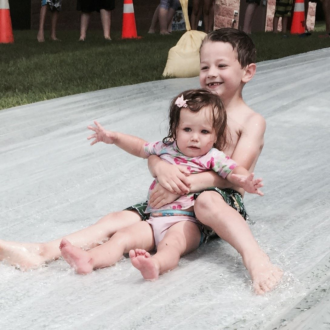 Two children slide together on a water slide