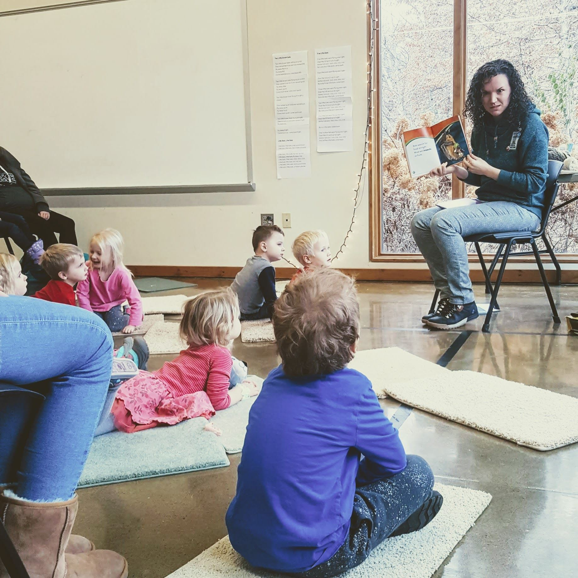 A librarian reads a book to children in the front row