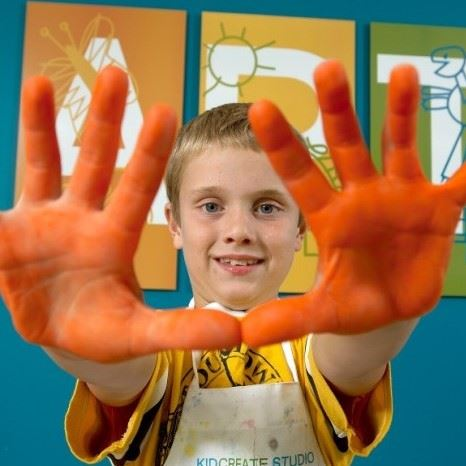 A boy smiles as he holds out his hands covered in orange paint